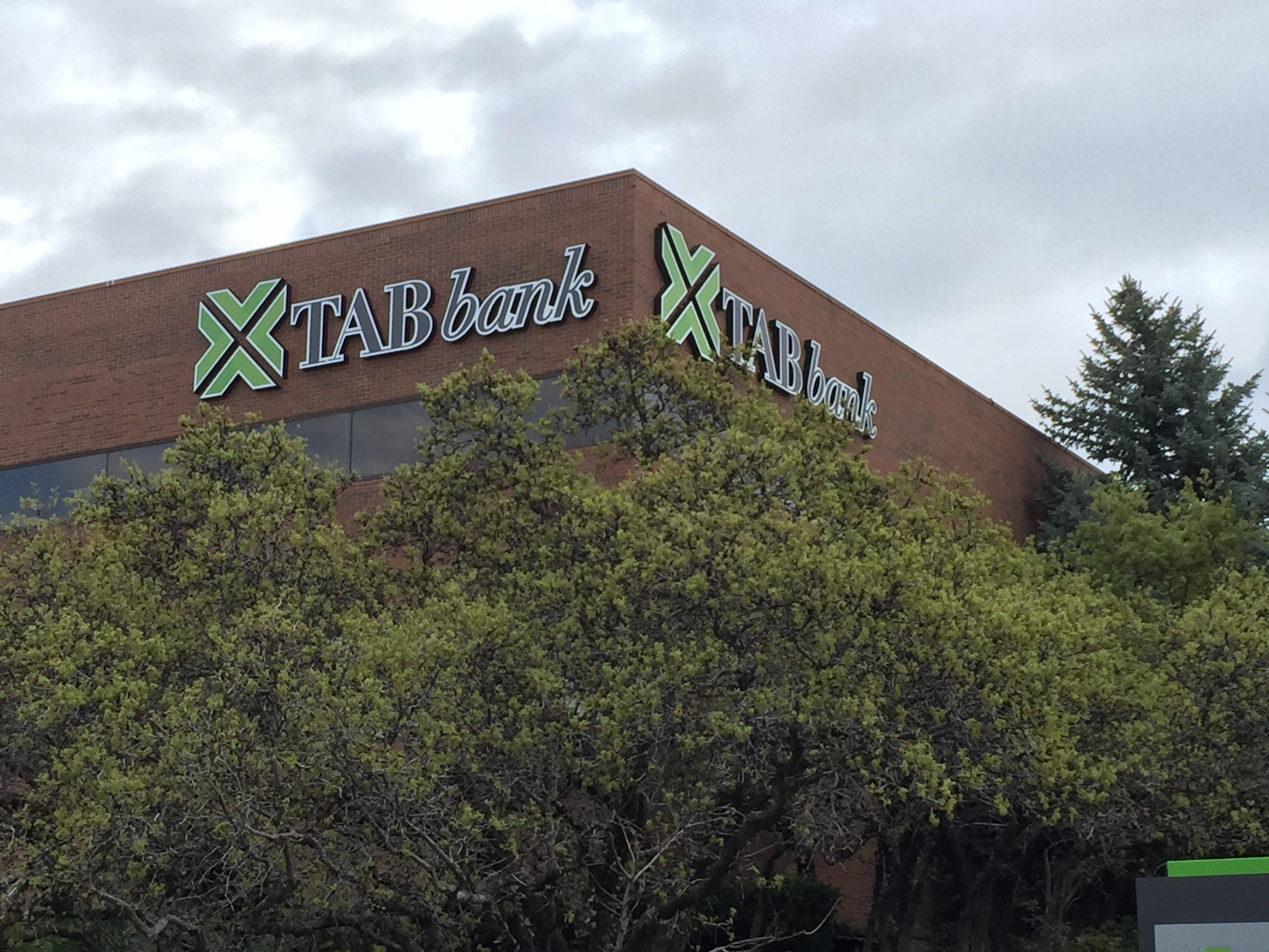 "A brown building with the words ""TAB bank"" written on it, behind a collection of trees covering the lower part of the building. - TAB Bank"